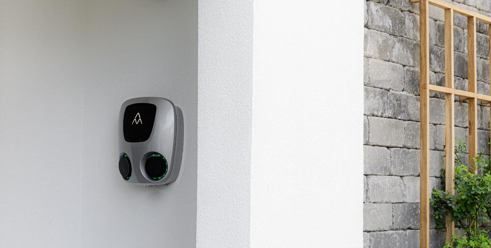 Charge Amps Aura installerad på vit stenvägg